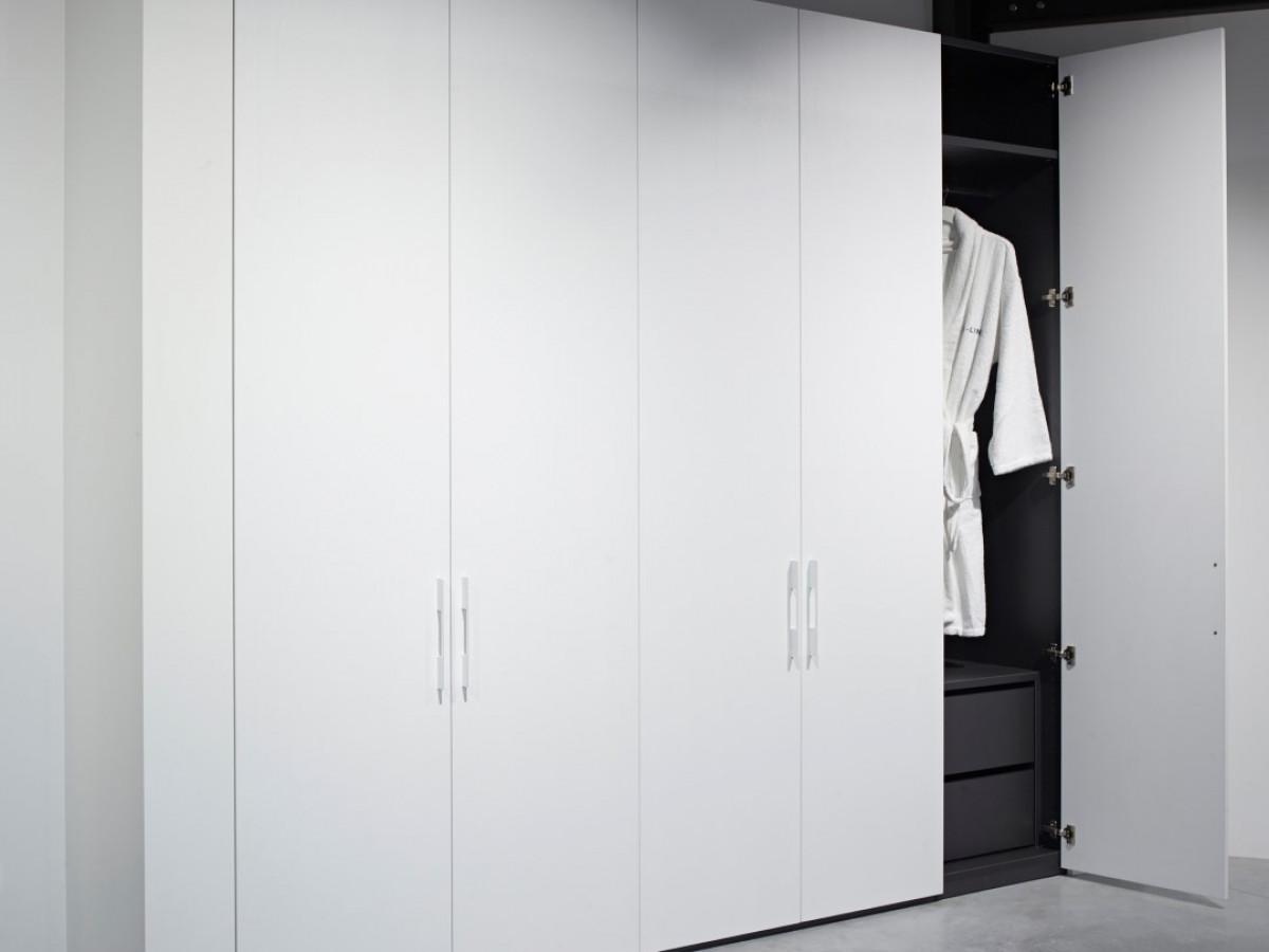 Maatkast combinatie witte draaideuren en donker interieur