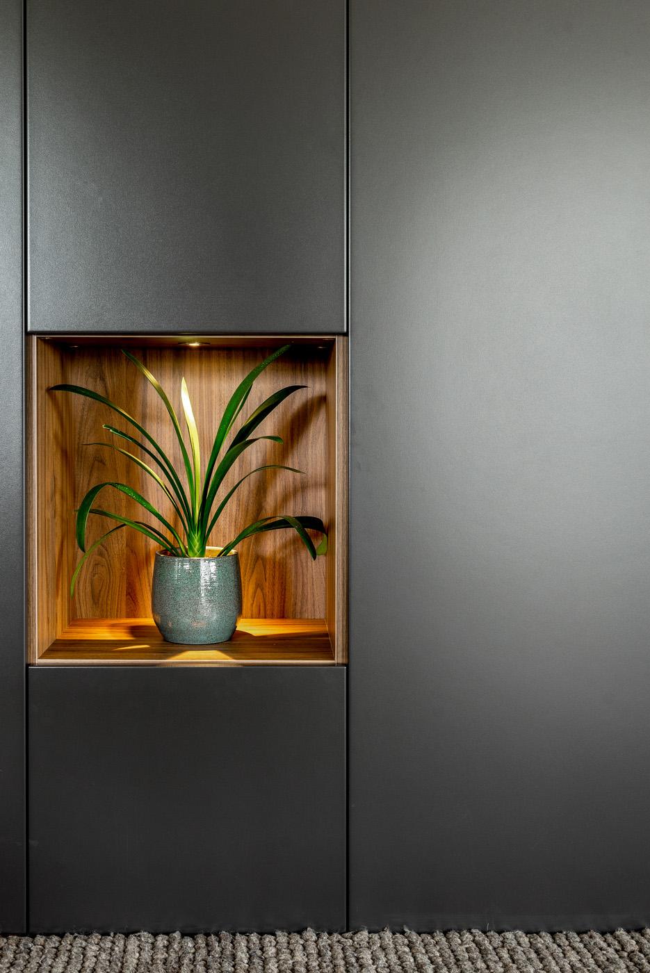 Detail wandkast in living met ingebouwde verlichting