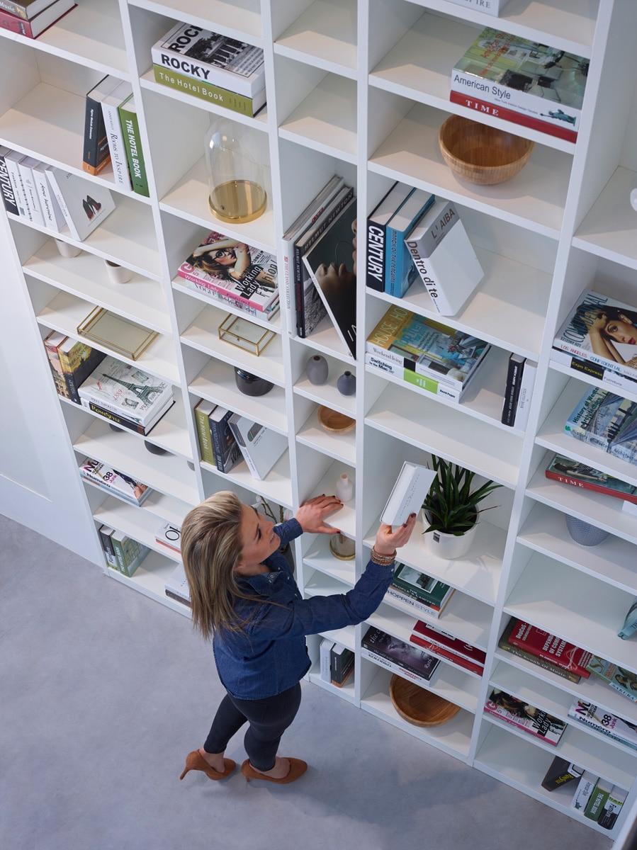 Boek nemen in hoge boekenkast