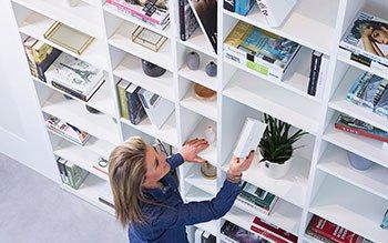 Vrouw neemt boek uit bibliotheekkast