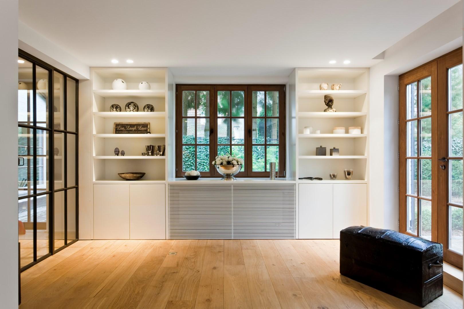 Grote witte wandkast op maat in de woonkamer