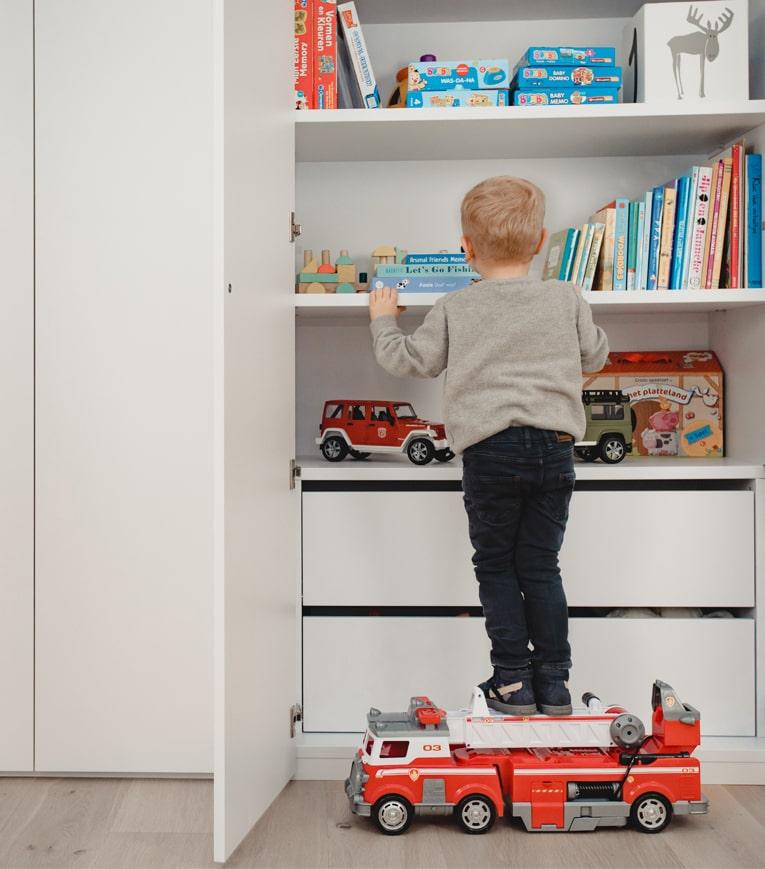 kind zoekt speelgoed in opbergkast op maat