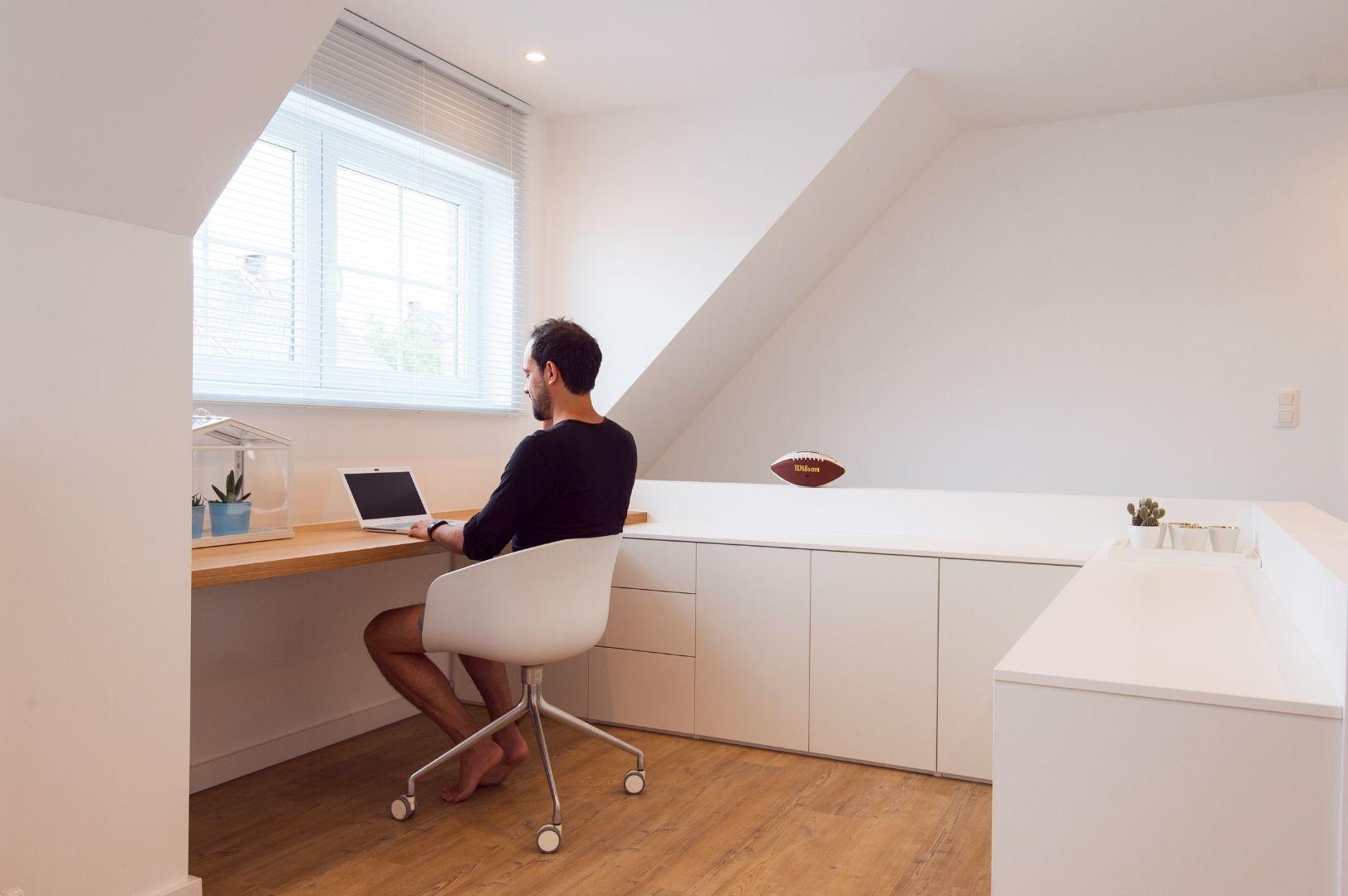 Man aan het werk in home office met witte maatkasten en bureau