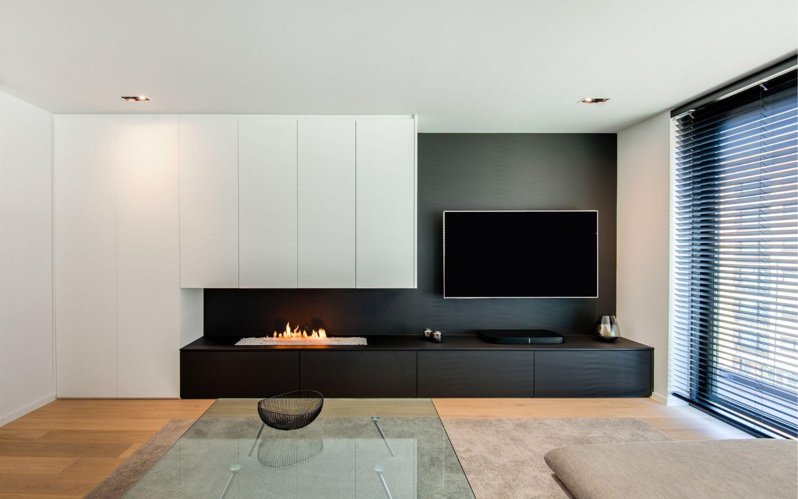 Tv-meubel met ingebouwde gashaard en wandkast waarin een bureau verborgen is