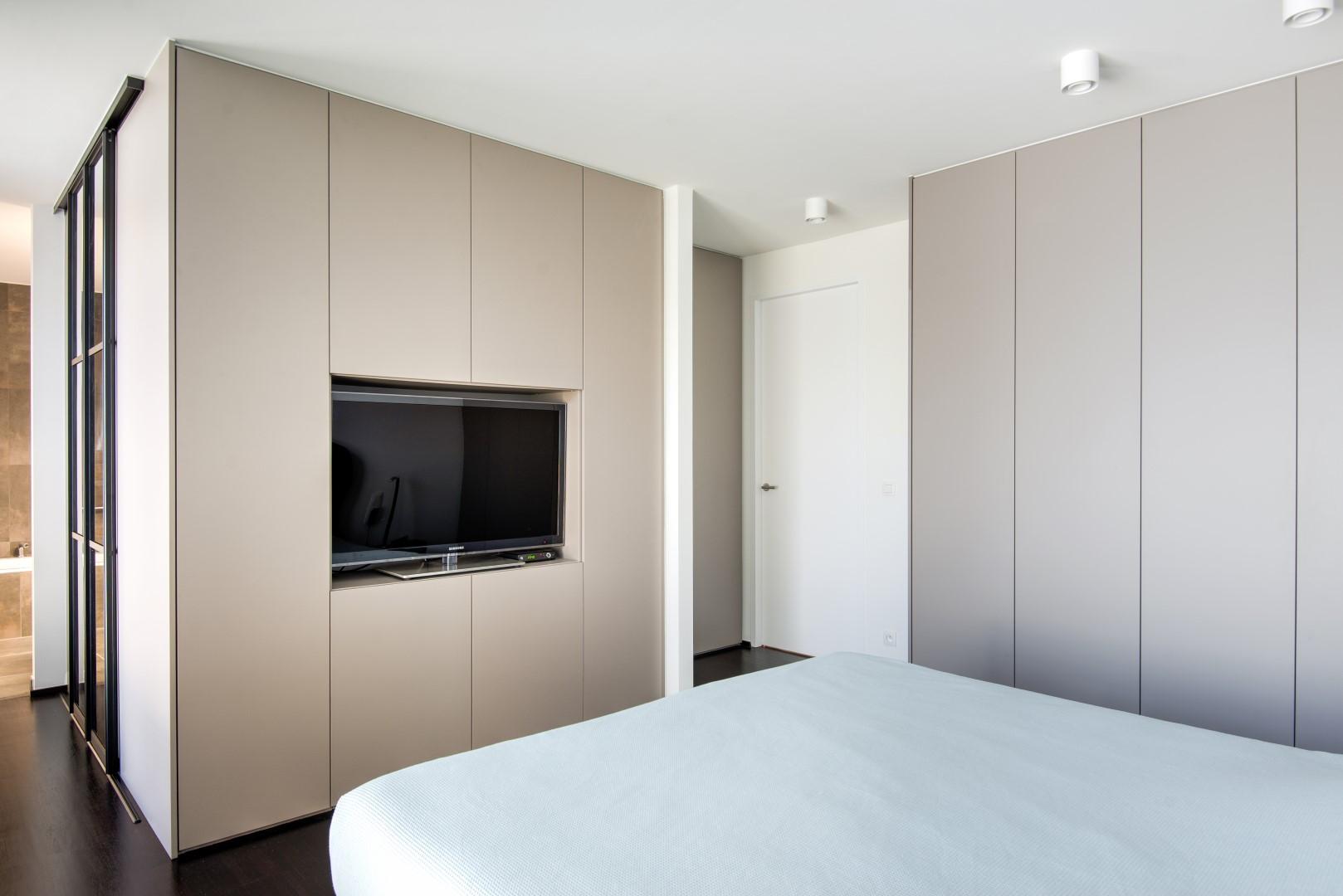Maatkasten in slaapkamer met ingebouwde TV waarachter een dressing schuilt met een scheidingswand als inkom