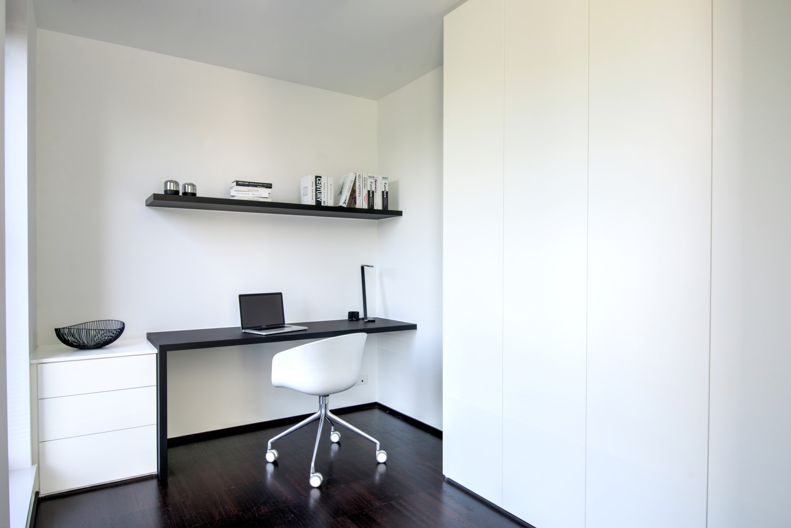 Modern bureau in nieuwbouwappartement met zwart-wit contrast