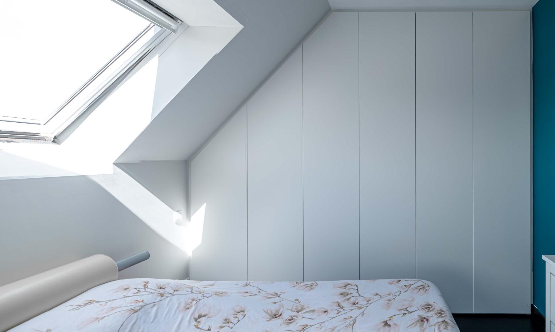 Moderne witte slaapkamerkast onder het dak