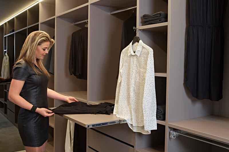 Vrouw vouwt kleding op in een droomdressing op een uitschuifbare legplank
