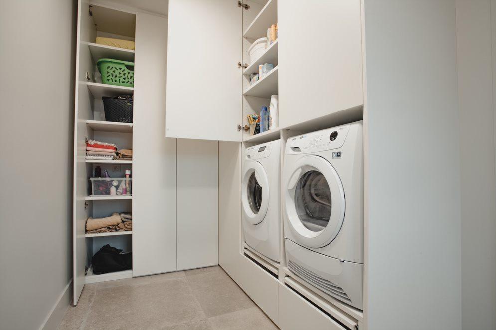 Functioneel ingerichte wasplaats met opbergkasten voor de wasmand