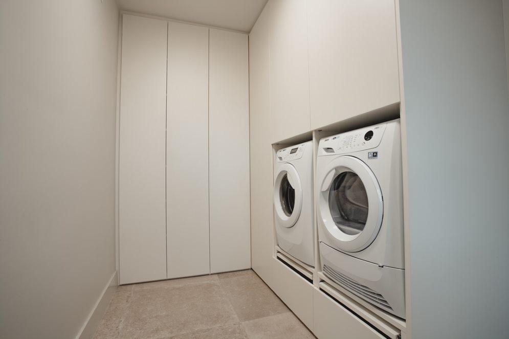 Functioneel ingerichte wasplaats met wasmachine en droger op hoogte